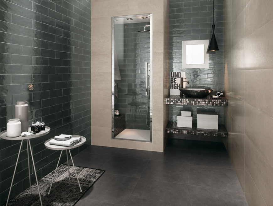 This modern bathroom is tiled in large, beige tiles on the right, and dark subway tiles to the left and behind the shower enclosure. Glass tiles cover the vanity with a simple vessel sink.