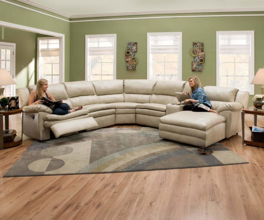 Soft wheat toned leather wraps this thick cushioned sectional, a lengthy piece incorporating both a recliner and full chaise lounge on opposite ends.