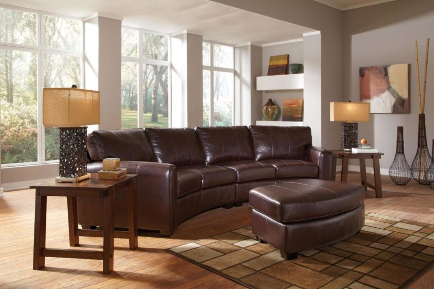 This thick cushioned, dark leather sectional pairs a set of love seat-sized pieces with a complementary, curved ottoman in matching tones.