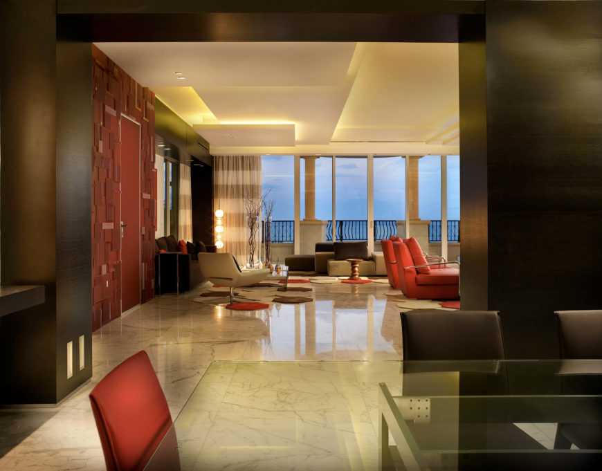 The open dining room looks into the formal living room, with a balcony and more floor-to-ceiling windows.