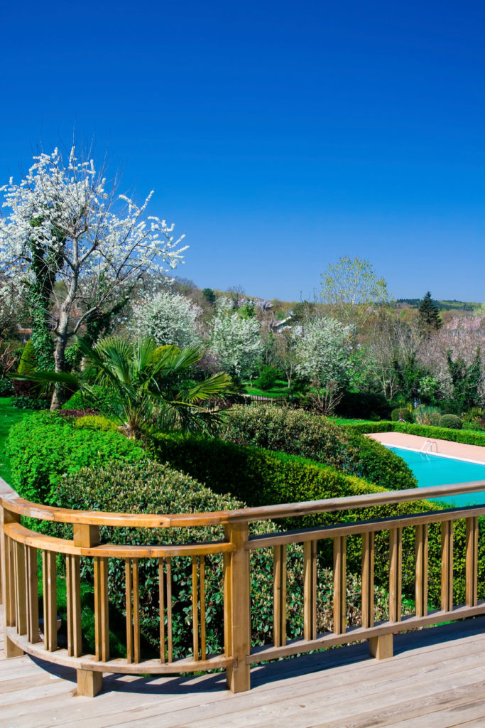 A raised deck that overlooks a pool complex with manicured hedges.