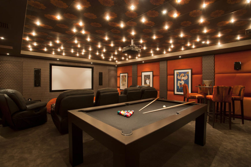 The home features this sprawling, mood-lit entertainment room, replete with cinema style seating and large pool table. Burnt orange walls, tiled ceiling, and constellation of recessed lighting create a unique look.