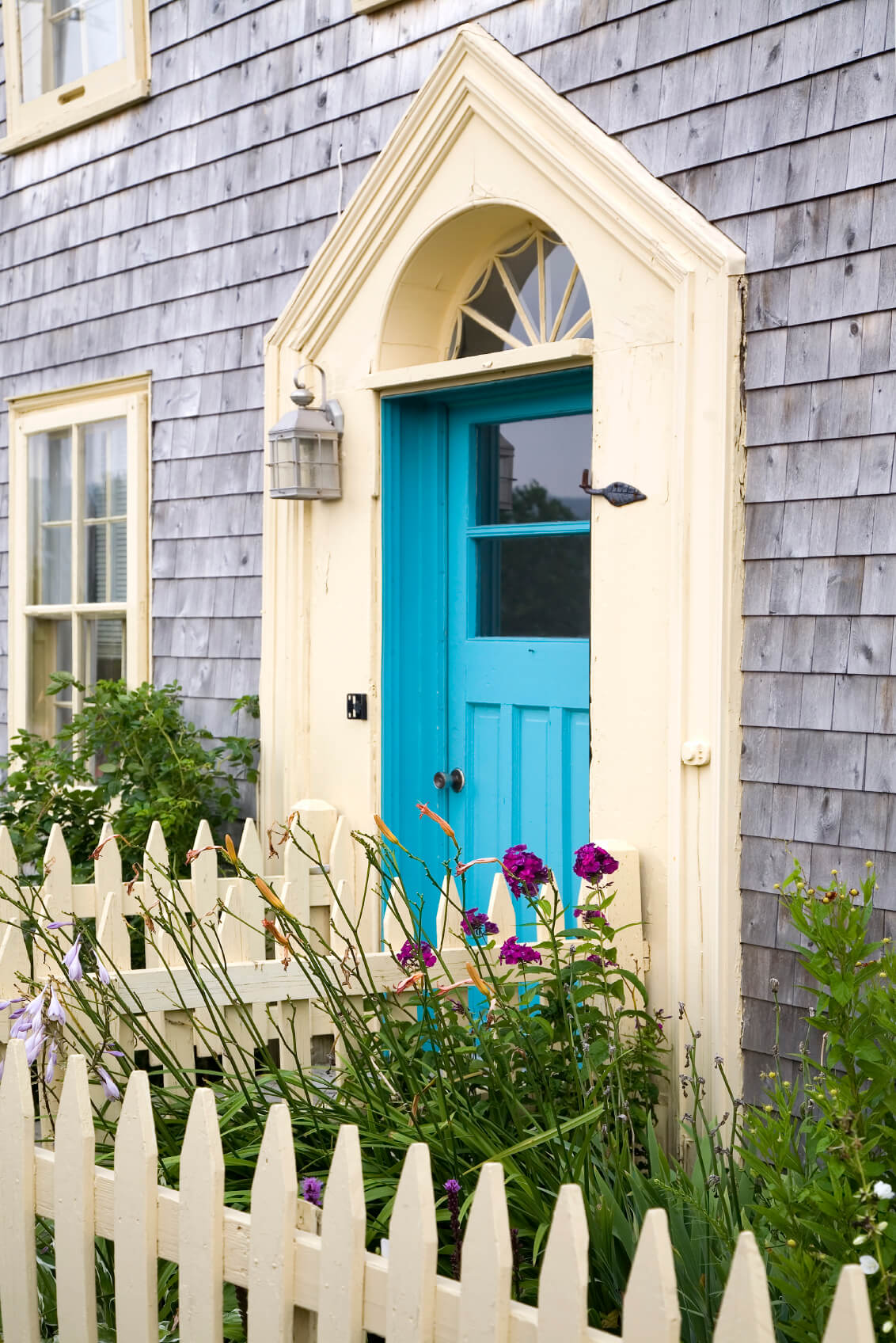 The front door is painted neon blue and beige as well. The door has a window and a transom right above it.