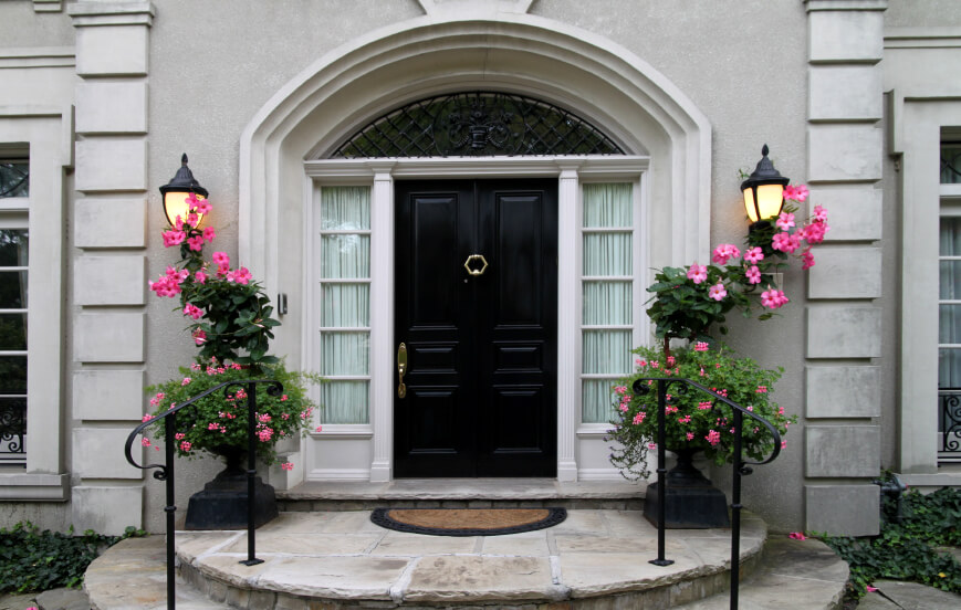 This home features circular stone steps leading toward a detailed black door with hexagonal brass knocker at center. The large arched doorway and windows frame the door in brighter tones.
