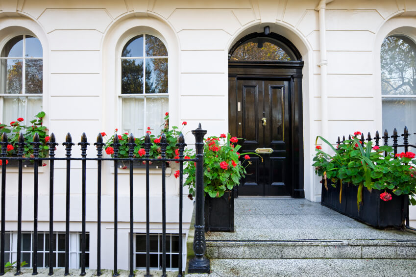 Soft grey granite steps and cream toned facade make space for this stately black door. The arched window design is echoed in the transom above the door.