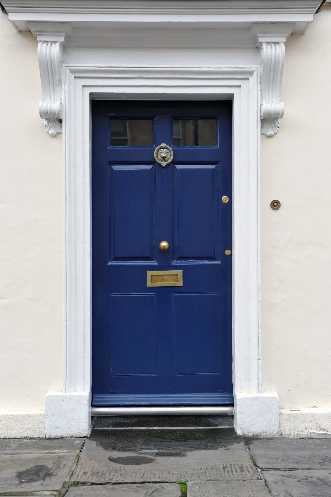 The main entrance has a white concrete facade. It has a blue door with a shiny brass knob right in the middle of it. The door also has a sculpted lion brass door knocker, lock, doorbell, and mail slot. The top part of the front door has glass panels. The door has a white brick molding.