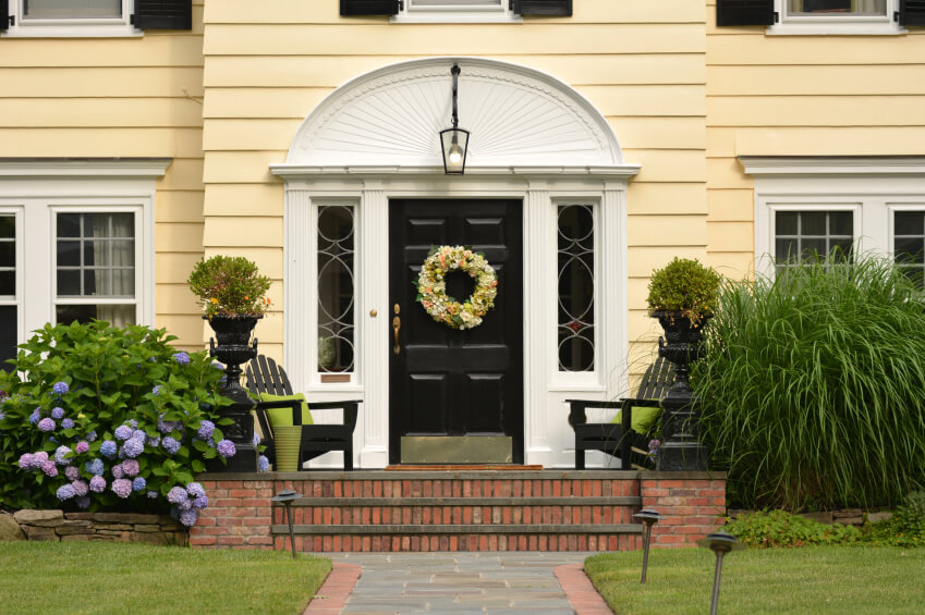 Yellow traditional home with a black front door