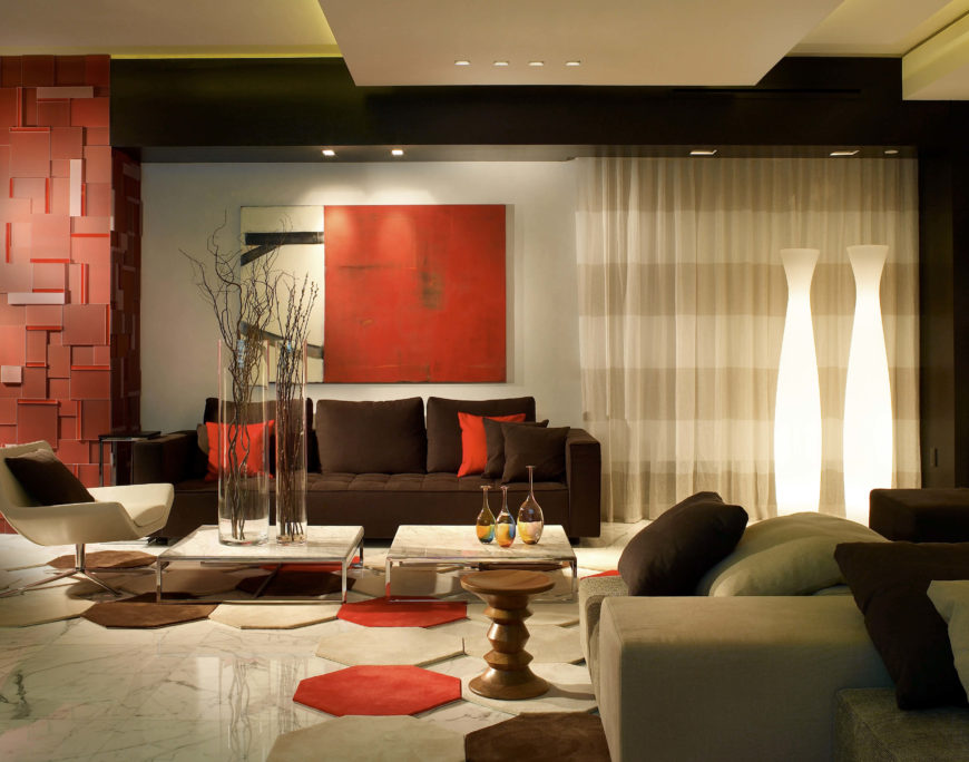 The modern living room has a color palette of taupe, chocolate brown and bright primary red. The marble tile flooring has a unique rug made up of hexagons with diamonds of the floor beneath peeping through. The squat coffee table on the left has two tall transparent glass vases of varying widths. The subtle striped airy curtains on the back wall add a bit of pattern to the room.