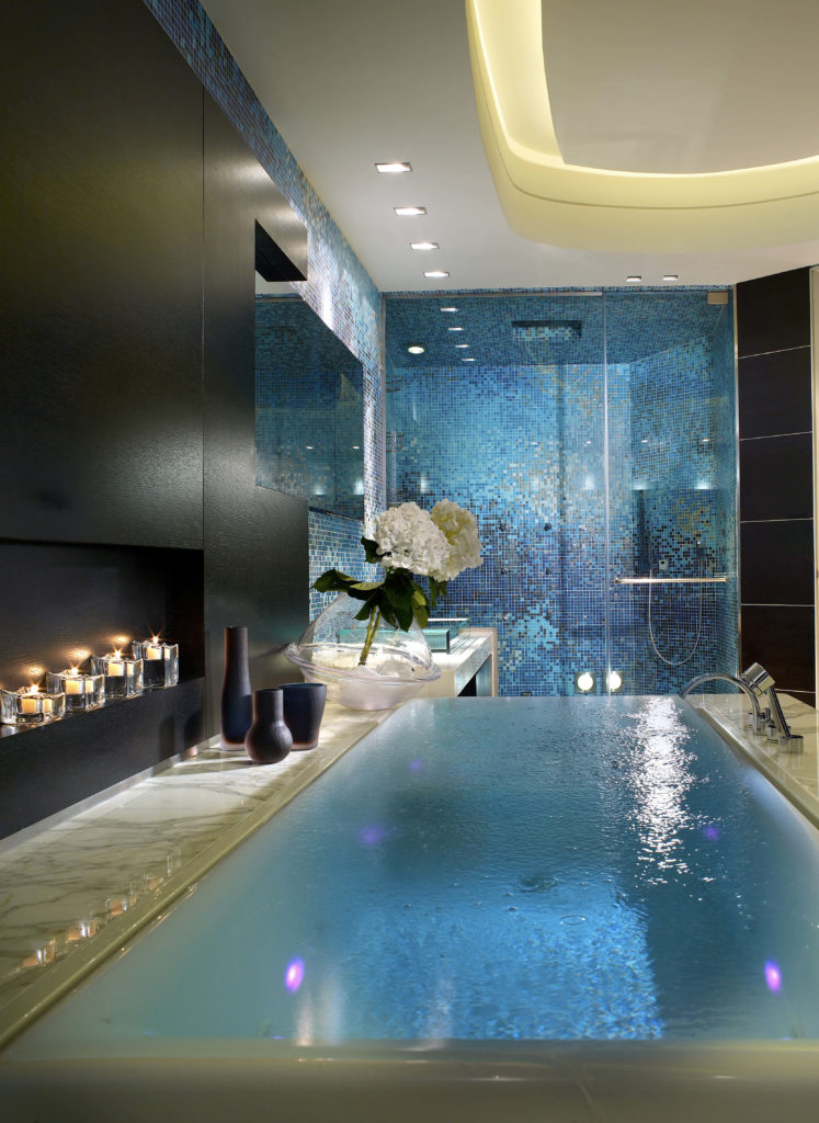 The large soaking tub is designed to resemble an infinity pool, and has a small shelf on the left holds a series of tea lights in glass holders for ambiance.