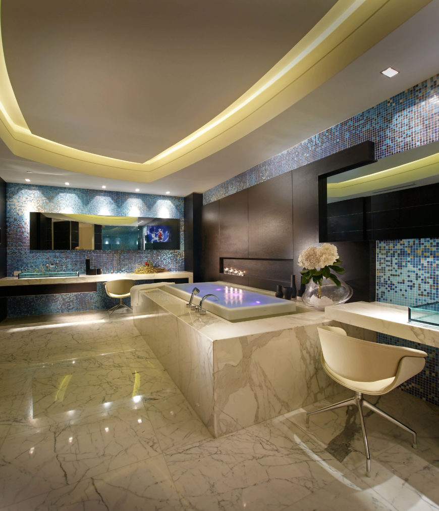 The spacious primary bathroom has an enormous tub, makeup table and tiled walls in shades of blue and brown. The tray ceiling is lit around the perimeter.