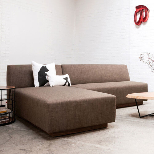A minimalist example of a modular sectional, shown here in a light brown with a walnut wood base. This simple bi-sectional can be rearranged to fit the space as desired.