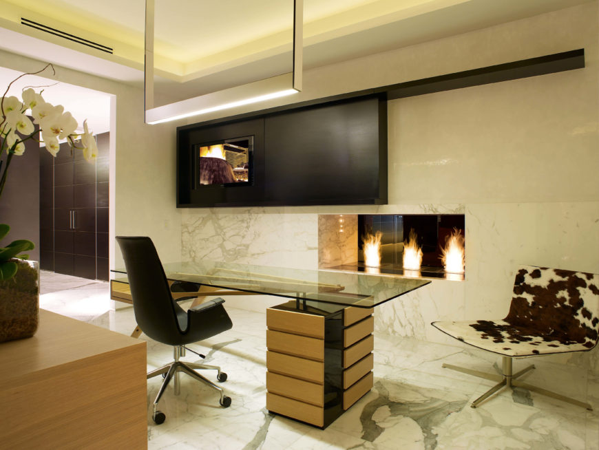 This view from the other side of the home office shows the pass-through fireplace and a television screen above and to the left of the fireplace, embedded in the dark wood panel.