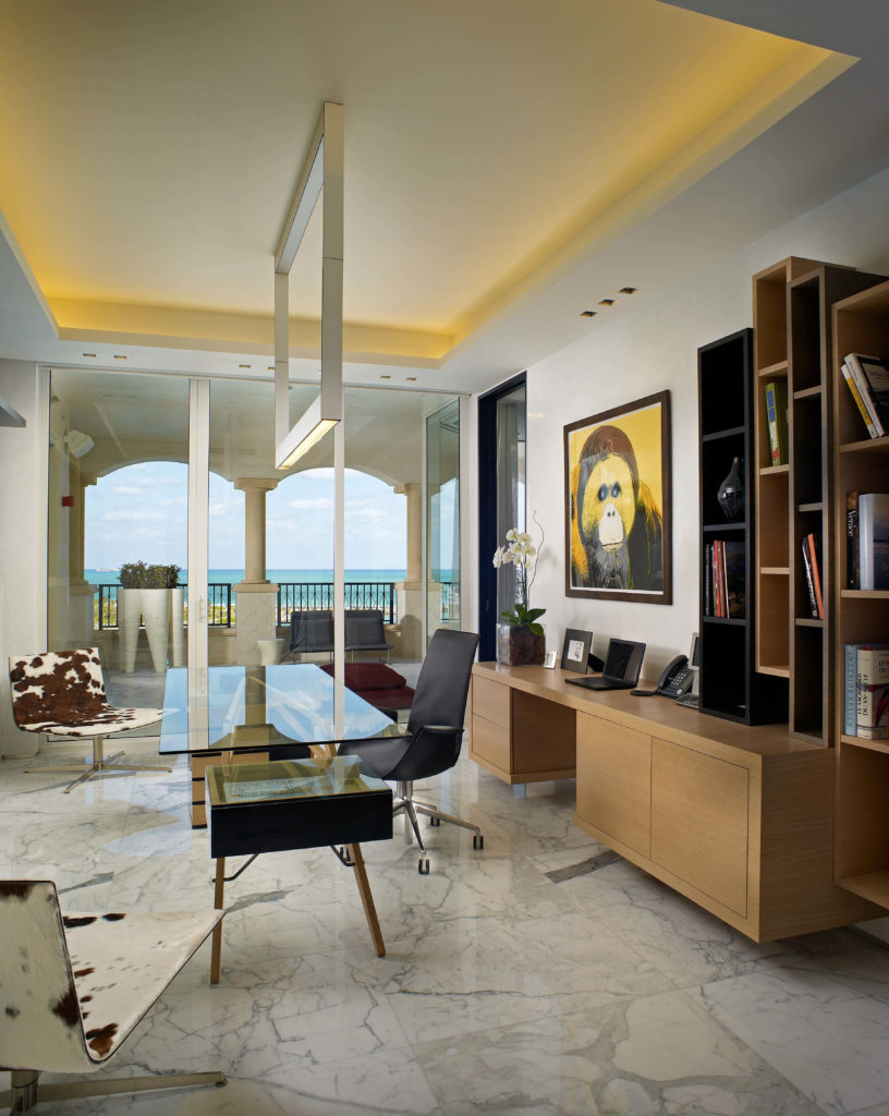 The spacious, light and airy home office takes a departure from the bold reds of the living room in favor of a set of cowhide print chairs and other black chairs. The desk consists of two separate working spaces. The glass table acts as a meeting table, while the minimalist natural wood desk behind it is more of a command center, with the laptop and phone.