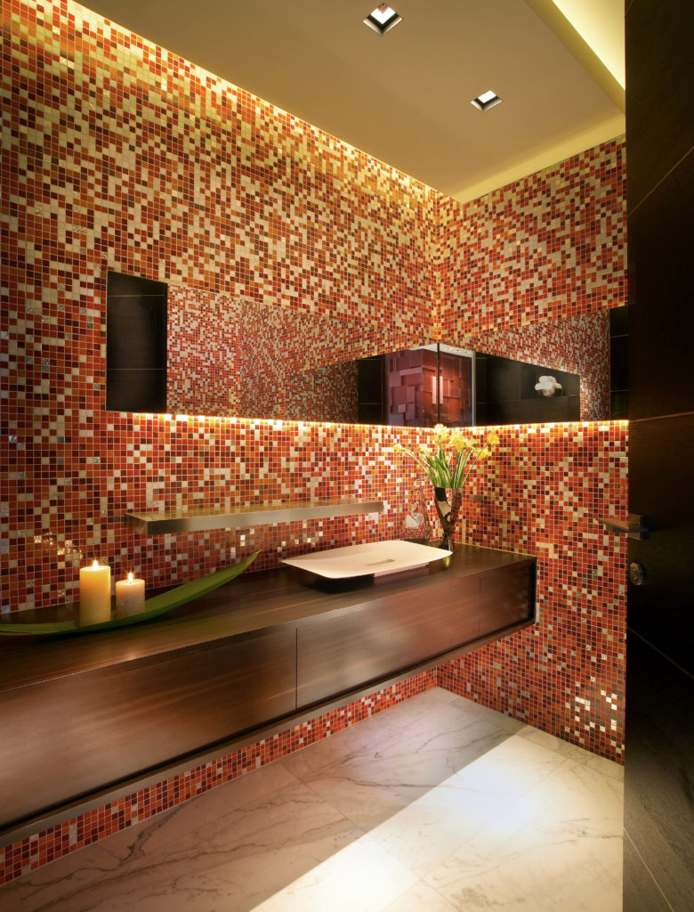 The powder room is a mix of modern and contemporary. The marble tile flooring continues into this room, and is paired with red tile from the floor to the ceiling, with smaller flecks of metallic, beige, and brown tiles scattered throughout. The elegant floating natural wood vanity adds elegance.