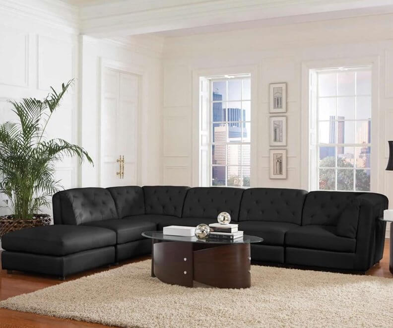 A black leather sectional with an ottoman that can be attached to either side to create a chaise lounge. The back cushions are tufted and have thick padding for extra comfort.