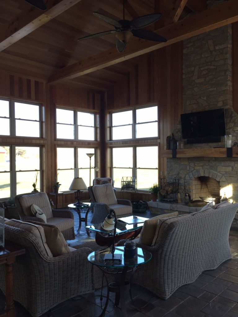 Here we see new ceiling fans installed on the exposed beams, as well as the large mantle, matching the ceiling look.