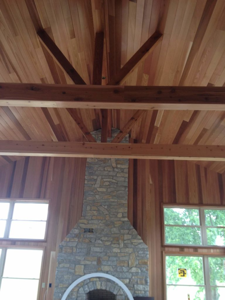 The natural wood exposed beams in the vaulted ceiling are an architectural highlight in the home. The stone fireplace creates a perfect rustic contrast.