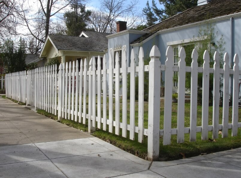 A traditional white-picket fence, although a bit taller than usual, surrounding this pretty blue stucco home.