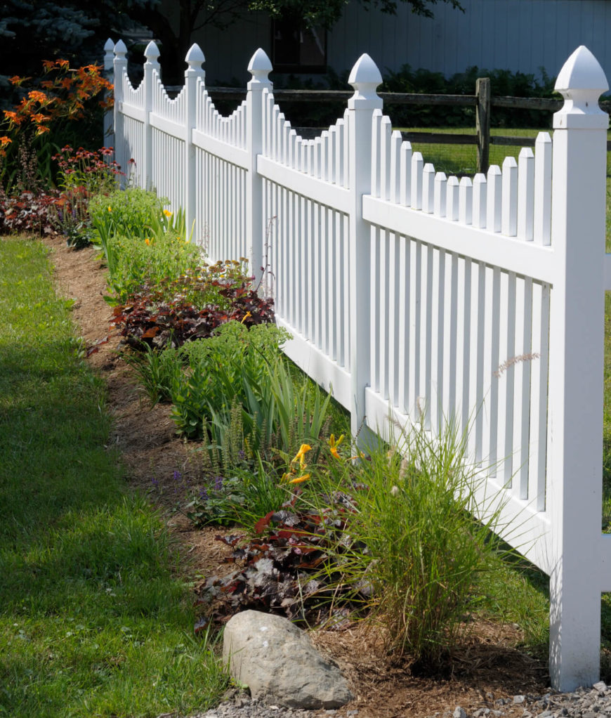 A white picket fence with simple, pretty landscaping.
