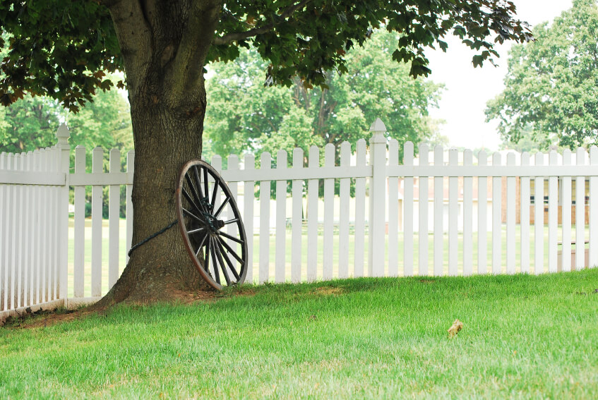 A white picket fence surrounds a tree with an old wagon wheel chained to it, giving this scene a country feel.