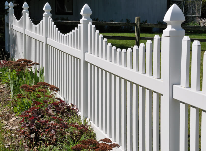A white PVC picket fence with simple landscaping and a more rustic fence in the background.