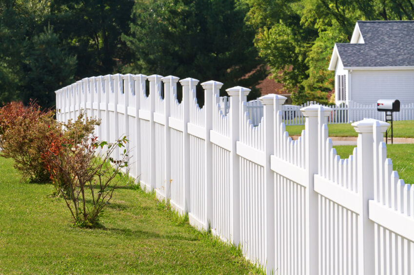 A more grand style of white picket fence, with taller pickets for privacy.