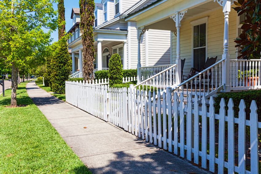 A white picket fence in traditional wood surrounding this older home in a downtown area.
