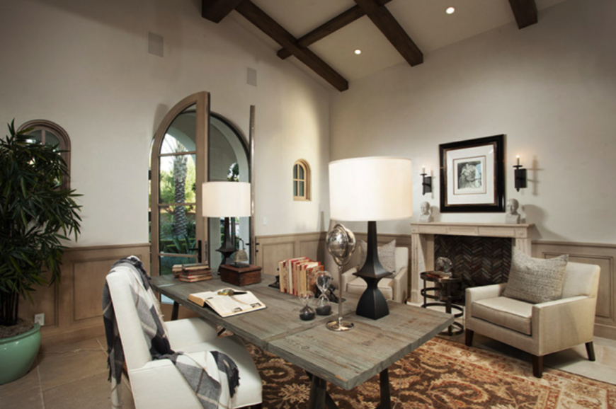 After staging, the room becomes a main-floor study with rustic details mixed with contemporary and modern features. An area rug warms the stone floors and pulls the desk and seating area together.