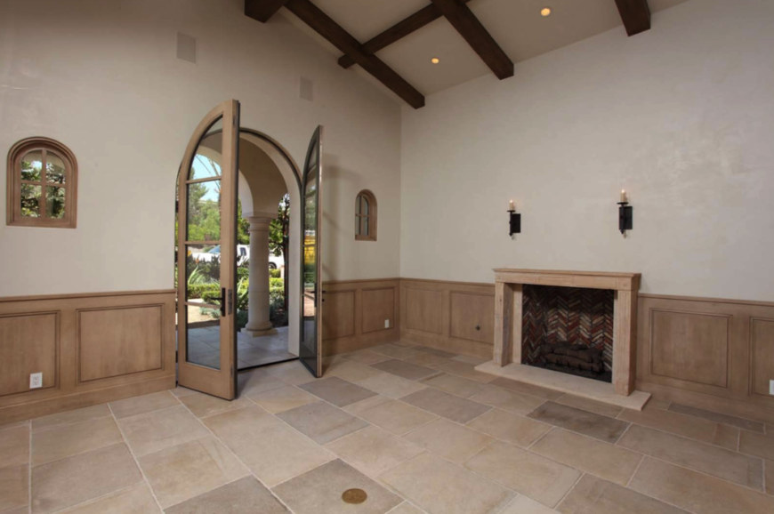 Like the bedroom, this room has a beautiful fireplace with two iron sconces above it. The French doors lead out into the front yard, and are flanked by two very small windows. The stone tile floor has subtle variation in color that add visual interest.