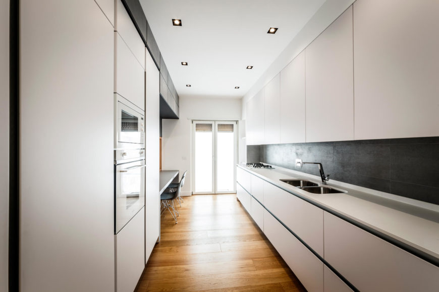 The kitchen stands as a lengthy, discrete element within the open space, defined by long countertops and a black backsplash, matching the dividing wall. A small in-kitchen dining space stands along the left side.