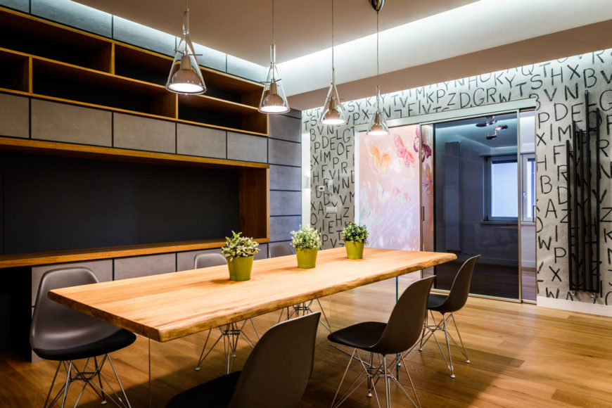 The dining room table is a singular slab of natural hardwood, surrounded by black and chrome minimalist chairs. The monolith wall stands at left, while the main hall is seen at right.