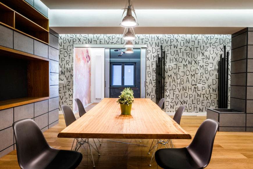 The open plan living and dining room is an exquisite buffet of details, including the letters wall at far end, monolith dark slab panels, modern lighting, and rich hardwood flooring.