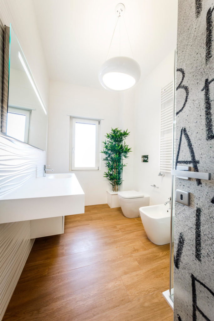The bathroom continues the white-on-wood motif, with a floating minimalist vanity at left and glass enclosed shower at right.