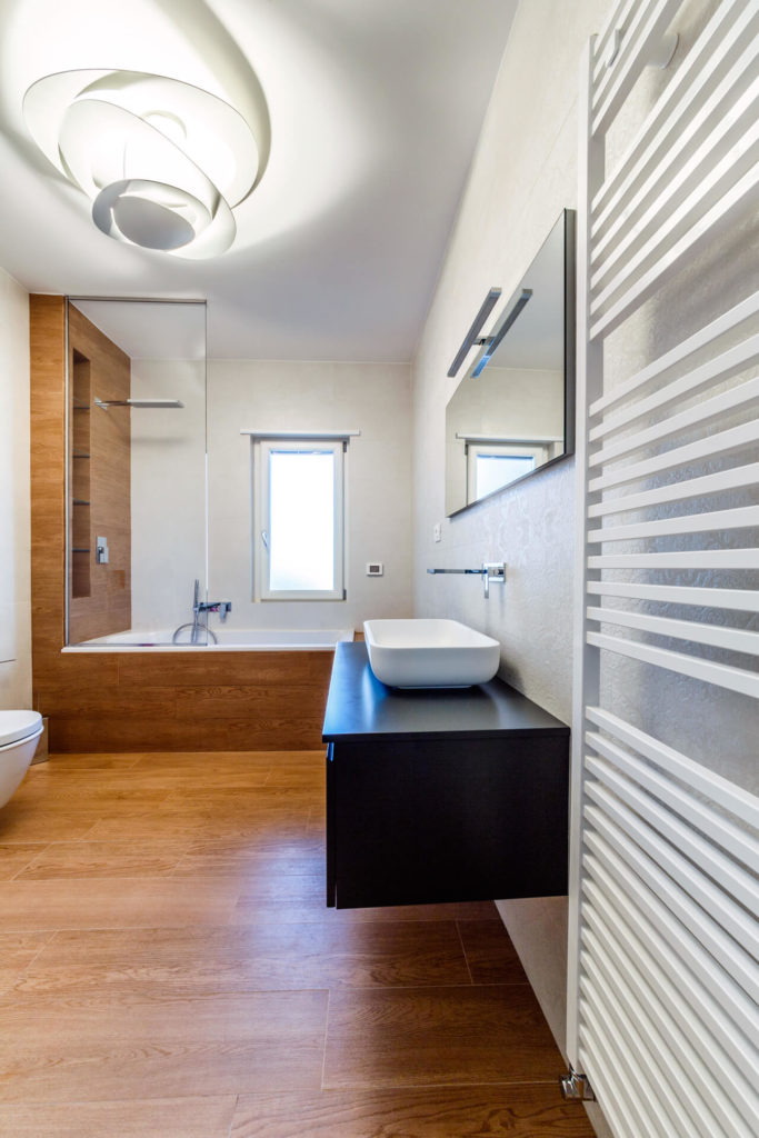 The primary bath is overseen by a large ultra-modern lighting solution in white, with wood wrapped soaking tub at far end. Floating vanity in black holds a white vessel sink.