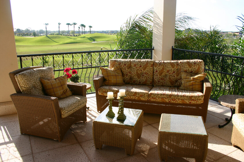 This pitted stone patio over looks a large golf course with some tall palms off in the distance. Wicker patio furniture with foliage and paisley patterns provide a comfortable area from which to enjoy intimate conversation or relax and feel the cool breeze coming off the water.