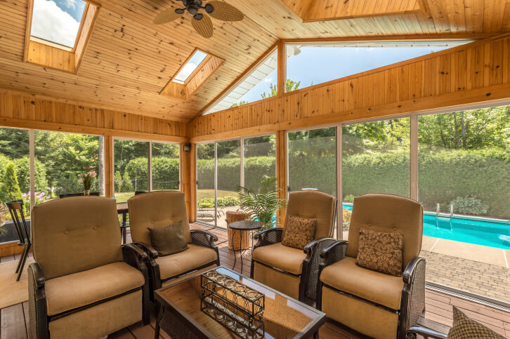 This fantastic sunroom offers a beautiful wooden theme, with multiple skylights on the ceiling. This natural pine paneling pops with the shimmer of the natural light entering from the windows and skylights.