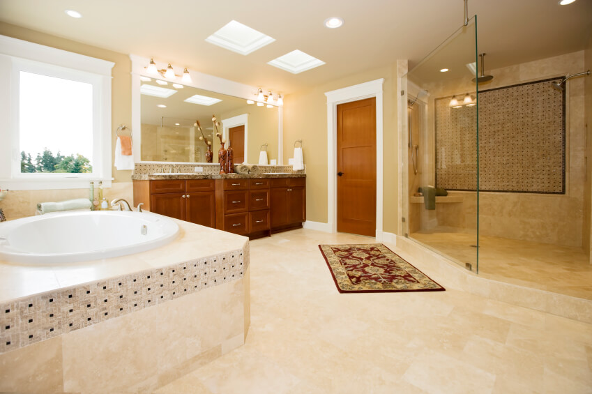 Another view of the previous bathroom shows a small oblong bathtub luxuriously encased in cream stonework with black accents. A window allows additional light to flood this already cheerful space.