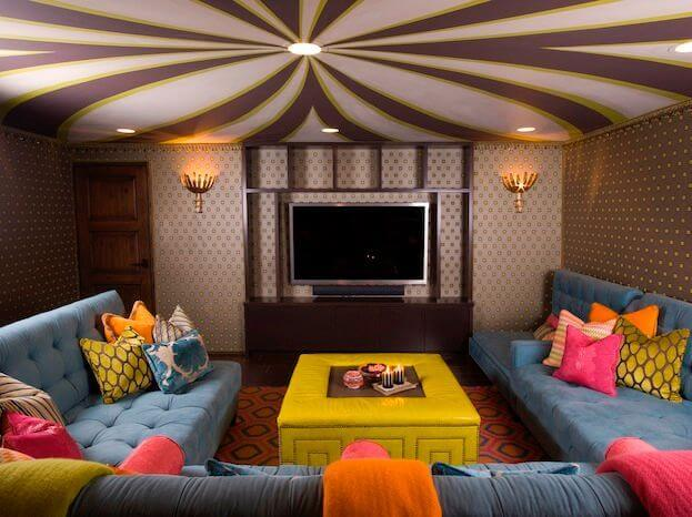 A wild and whimsical family room makes for a perfect movie night and sleepover hangout for the kids. The dusky blue sectional sofa is covered with brightly colored blankets and pillows, so each person can make their own cozy nest while watching television.