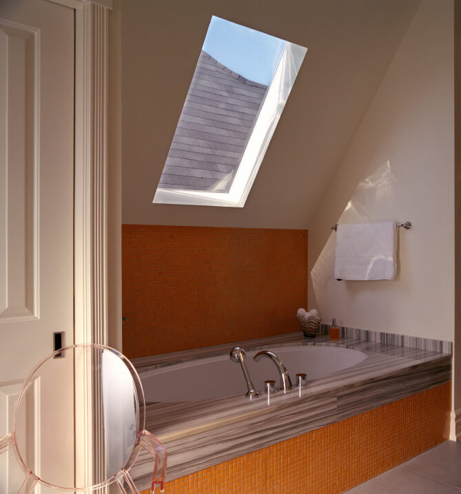 This skylight hovers above a bathtub encased in bold orange petite tiles and topped with exquisitely veined stone work.