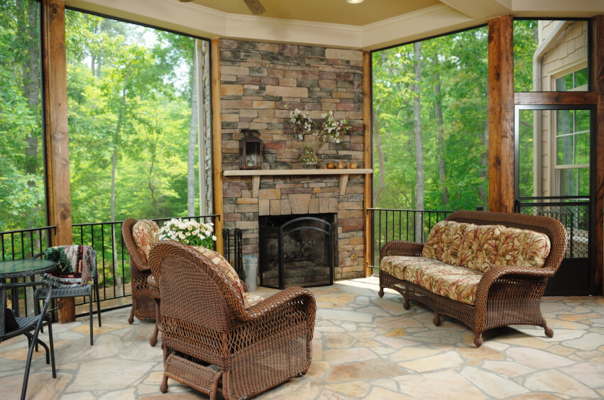 This lovely covered patio is also a three-season room with removable glass. The immense stone fireplace is both a statement piece and serves the function of providing warmth and atmosphere on a cold day. This patio is elevated and looks out on the forest, which gives it the air of a luxurious treehouse.
