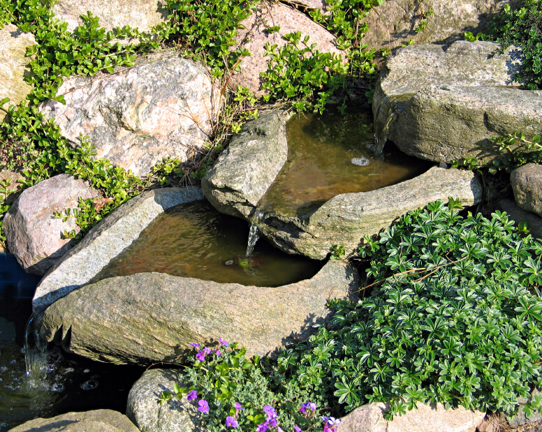 Vessel-shaped stone pools are stacked to crate a three-tiered waterfall tumbling into a small pool. Thick ground cover peeks up from in between the surrounding boulders.