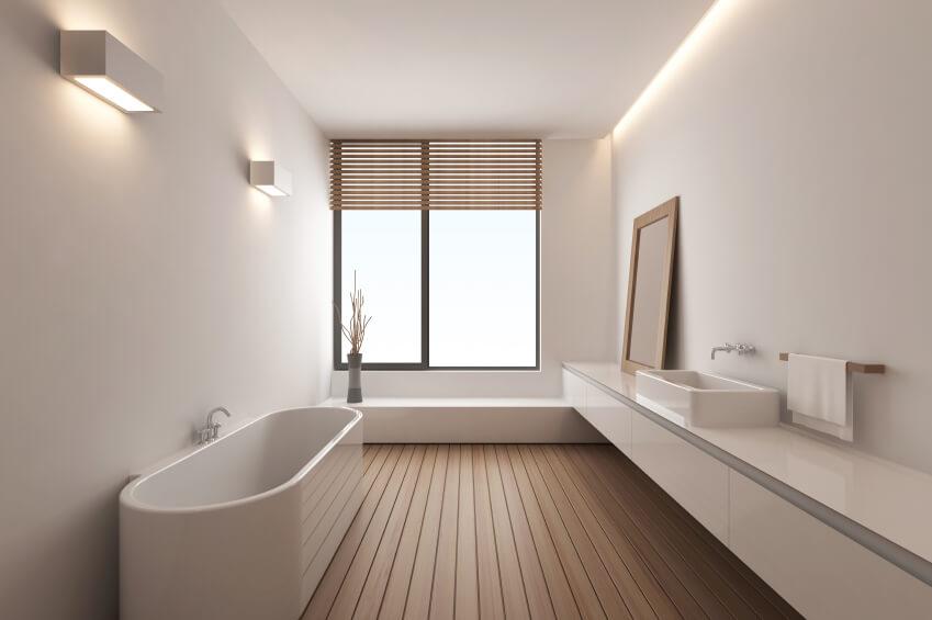Salle de bain principale moderne comprenant une baignoire autoportante et un lavabo ainsi qu'un plancher de bois franc entouré de murs et de plafonds blancs.