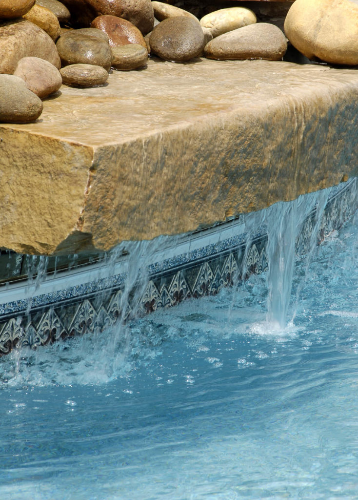 A waterfall made of a large concrete slab with round stone stacked above. A close up view of the tile around the perimeter of the pool shows the beautiful detail.