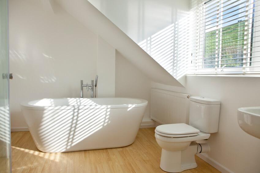 Salle de bain principale simple avec murs blancs, parquet, grande baignoire autoportante et salle de douche à l'italienne.