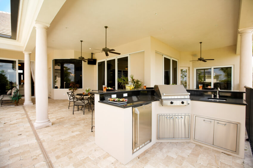 This outdoor patio is tucked beneath a large, deep veranda and includes a small outdoor kitchen, a dining area, and a seating area. Three ceiling fans keep air circulating and a small television in one corner is an added luxury.