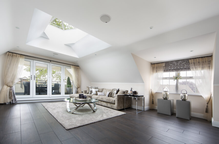 This simple living room with dark hardwood flooring and minimal furnishing features a grand skylight with two different geometrical shapes in one. The skylight pulls up from the actual roofing itself to bring as much natural light into this contemporary living room as possible.