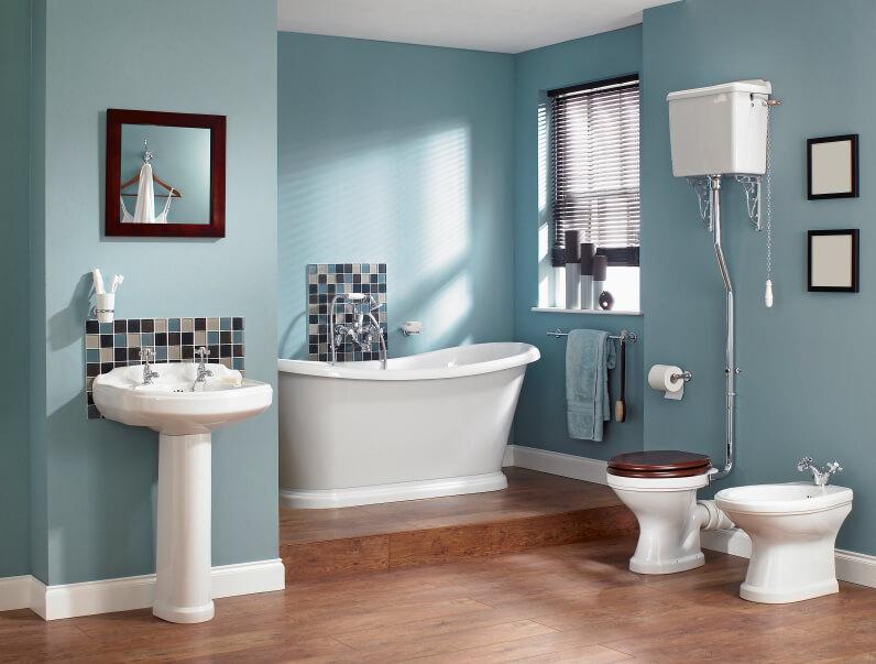 Salle de bain principale avec parquet et murs bleus, baignoire autoportante et lavabo sur colonne.