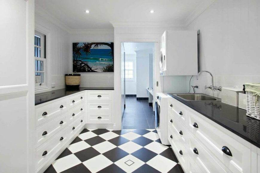 Just off of the main hallway is the laundry room, which continues directly into the main floor mudroom and bathroom. The checkerboard flooring and white cabinetry with glossy black countertops is a design that will be carried on later in the kitchen.