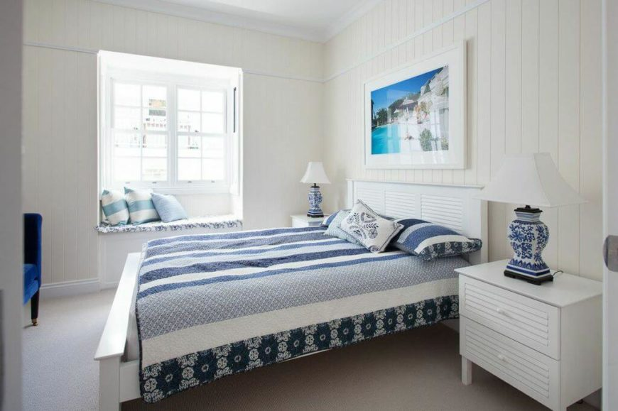 On the main floor are the bedrooms and bathrooms. Continuing the blue designs from the living room and foyer in the primary bedroom, the elegant patterns flow throughout the room, from the bedding to the lamps to the window bench seat.