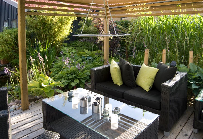 This small, yet elegant covered wood patio boasts a glass-topped black wicker coffee table between matching wicker sofas and chairs. The space is lit at night by a circular ring light. Three sides of this small garden patio are filled by thick, lush landscaping.